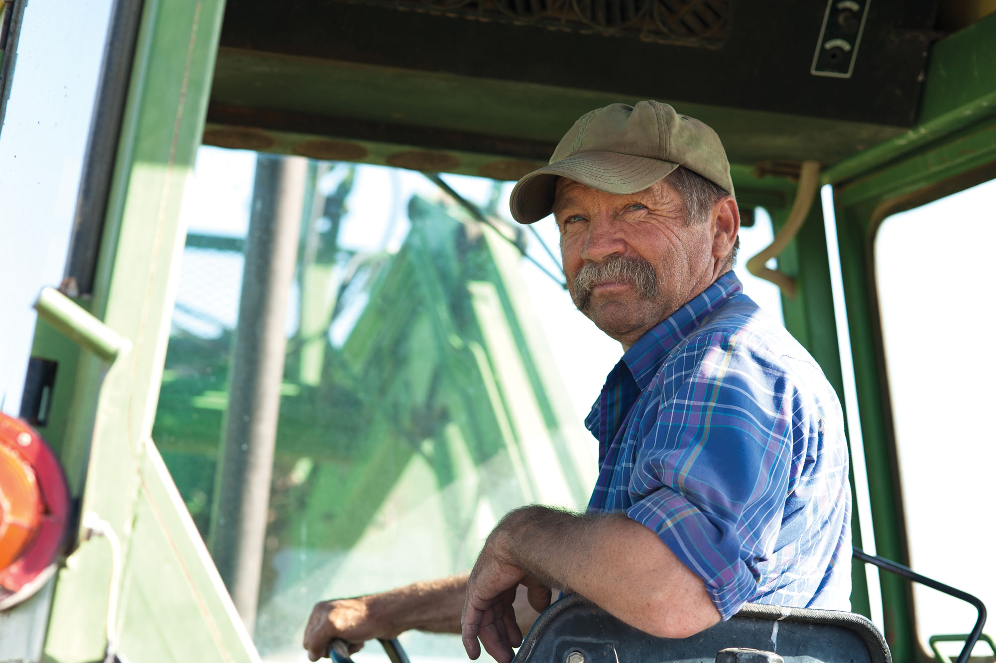 Smiling farmer on tractor looking over his shoulder